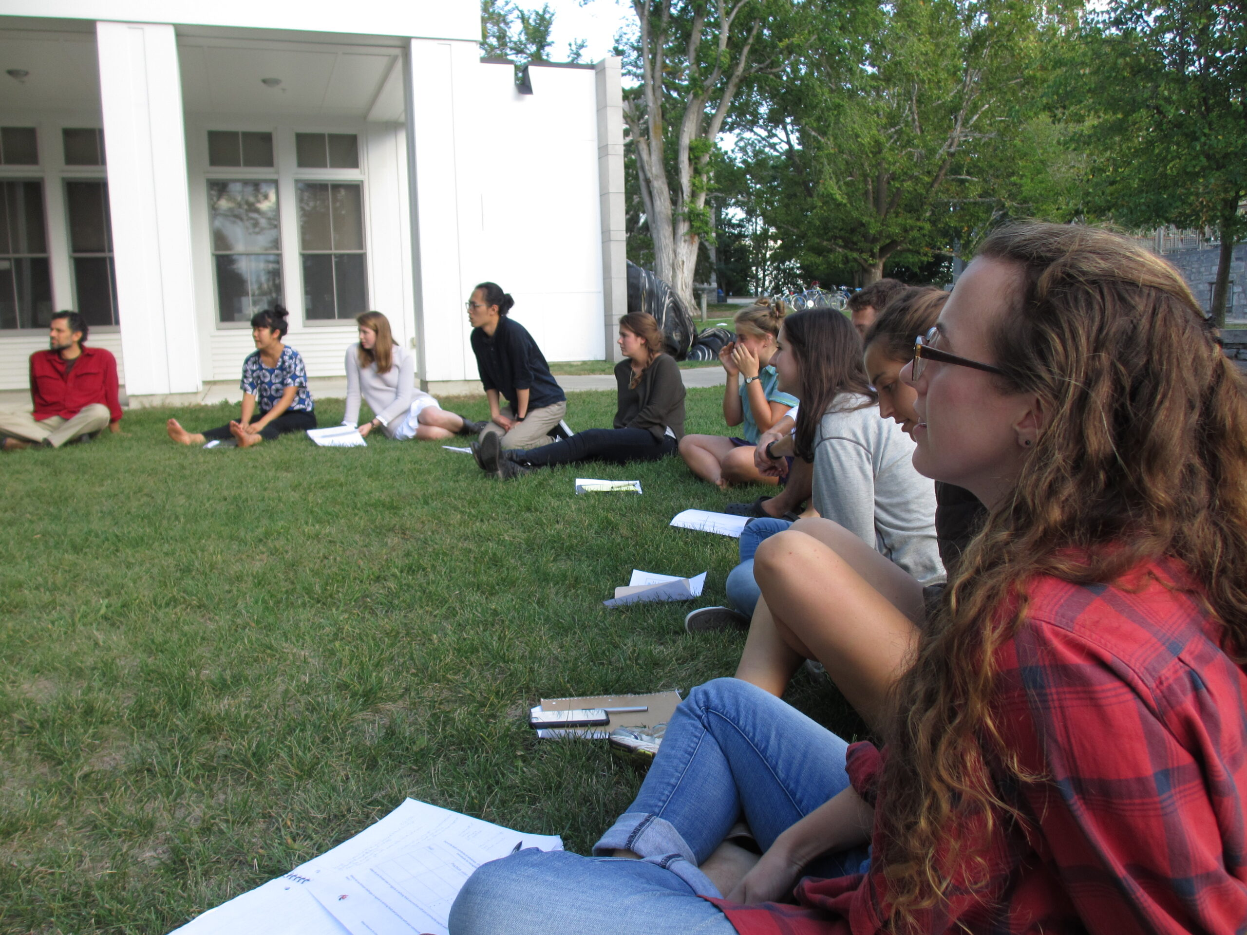 Students in a semi-circle sitting outdoors